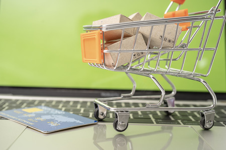Selling or buying online,shopping online or e-commerce with paper box ,paper bag and credit card in shopping cart or trolley. Archivio Fotografico