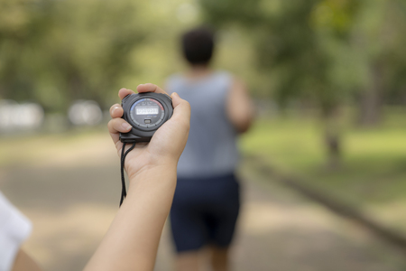 hand holding timer watch for jogging in park.