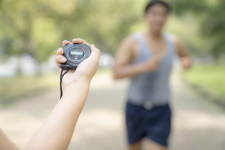 hand holding timer watch for jogging in park. Archivio Fotografico - 111266460
