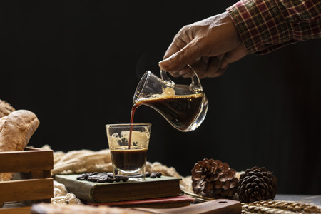 hand holding cup of coffee and pouring to clear glass in coffee shop. Archivio Fotografico - 111266447