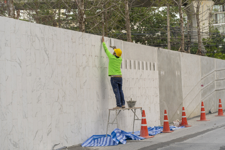 mason worker during installed white gray marble on the wall Stock Photo