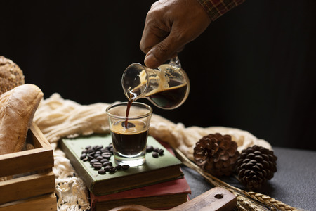 hand holding cup of coffee and pouring to clear glass in coffee shop.