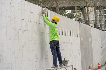 mason worker during installed white gray marble on the wall Archivio Fotografico - 112338477