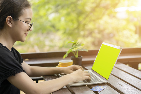 Young woman holding plastic credit card and using laptop computer for shopping online at coffee shop.green screen is clipping path. Archivio Fotografico - 112338481