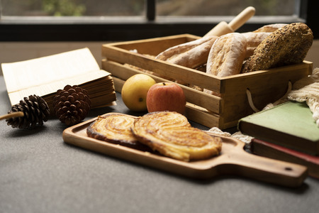 coffee and bread on wood tray in warm tone.