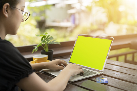 Young woman holding plastic credit card and using laptop computer for shopping online at coffee shop. Archivio Fotografico - 112338479