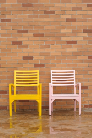 yellow and pink chairs on ancient red brick