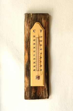 wooden celsius fahrenheit thermometer over white wall photo