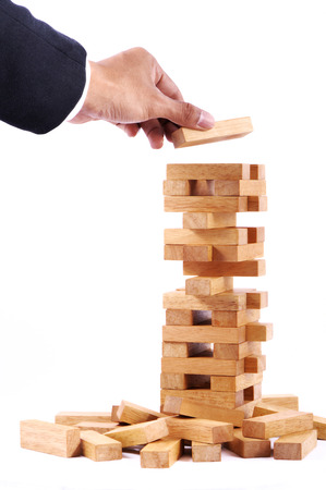 Businessman playing with the wood game (jenga).