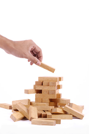 Hand playing with the wood game (jenga). on white background. Stock Photo