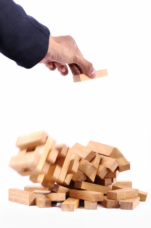 Businessman playing with the wood game (jenga). on white background.