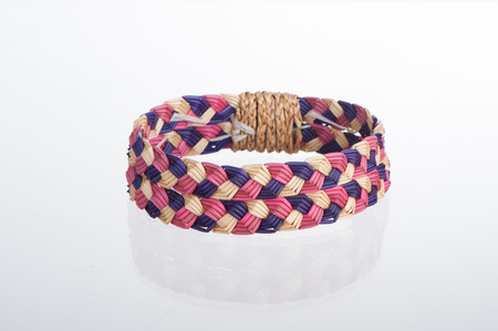 wristband made from woven straw on a white backgfround