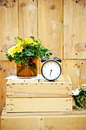 Old vintage alarm clock on wooden background
