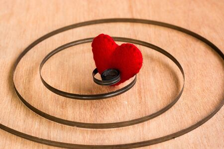 truelove: Red color heart shaped object in Chain on wood background Stock Photo