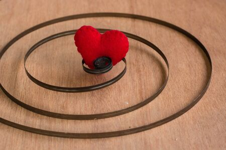 dearest: Red color heart shaped object in Chain on wood background Stock Photo