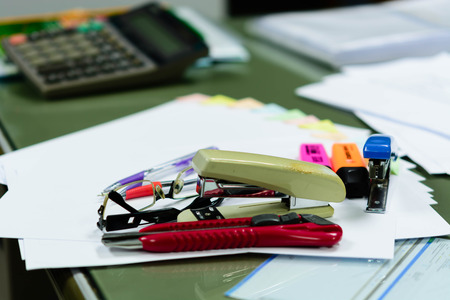 indicative: The file not that is placed on the desk a mess. Indicative of a lot of work. Messy workplace with stack of paper on table
