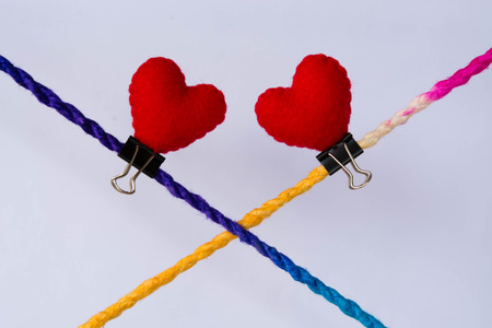 unbreakable: Connected group concept as many different ropes tied and linked together as an unbreakable chain as a community trust and faith metaphor. And red hearts above many Stock Photo