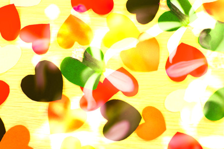 fasching: Yellow wood background with scattered colorful party confetti with heart shapes in a closeup full frame overhead view for festive or celebration themed concepts