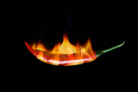 red hot chili pepper burns in fire on black background photo