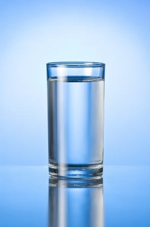 copa de agua: vaso de agua pura en el fondo azul brillante Foto de archivo