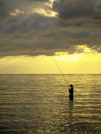 Silhouette of a man fishing in a sunset, Bali, Indonesia  photo