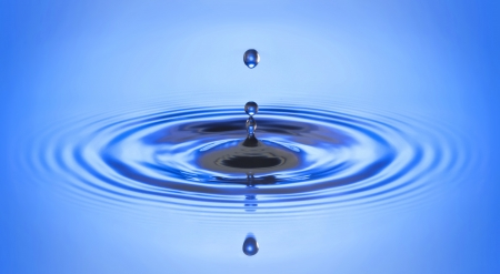 Water drop falling into water making a perfect droplet splash and ripple and wave  写真素材