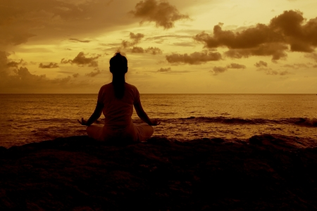 Silhouette of a beautiful Yoga woman in the morning on a beach rock by the sea, a girl in yoga lotus meditation position front to seaside at sunrise sitting photo