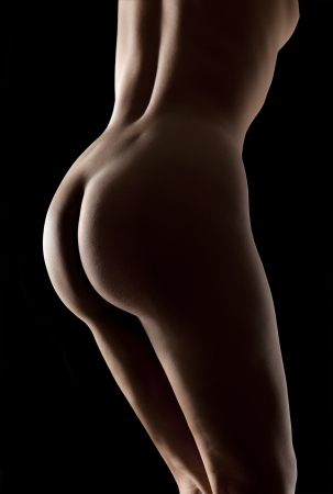 naked black woman: Close-up beautiful buttocks of a nude young woman in low key. Naked perfect sexy body isolated in black background