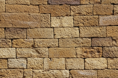 closeup of yellow sand stone wall, gold sand brick wall for background or texture 写真素材