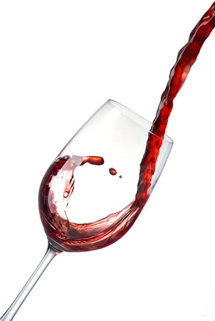 Pouring red wine into a crystal glass and creates waves, splash   Red wine poured from bottle into a glass isolated on white background
