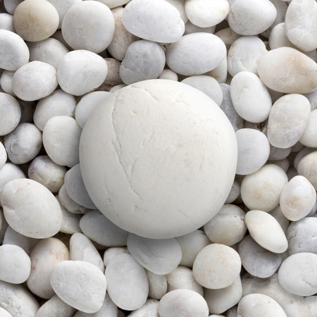white pebble: Big white stone laid on a pile of small round circle shape pebble, a group of rocks  Stock Photo