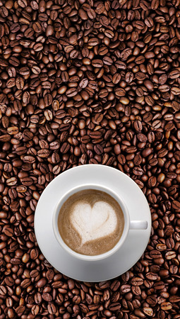 Top view - Coffee cup of LATTE ART, Love symbol, lover sign on top Pile of brown coffee beans with copy space for text or graphic design. Cafe latte cream on top coffee in heart shape on background of raw coffee beans. vertical Zdjęcie Seryjne