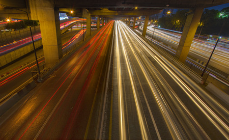 Car light trails on street, highway, expressway, motorway through the city in rush hour. Busy Road Traffic at big junction at night