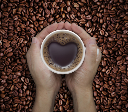 Coffee lover sign - man hands holding cups of coffee with heart shape on coffee beans background. love symbol on fresh coffee mug in male hands - Top view  版權商用圖片