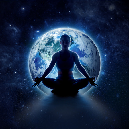 Yoga woman on the world. Meditation girl itting in lotus pose on planet earth and star in dark night sky.