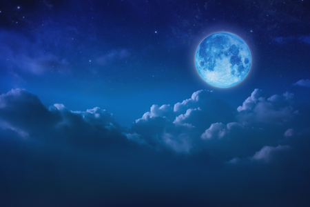 Full blue moon behind cloud over sky and star at night. Outdoors at night. Beautiful lunar shine moonlight over cloudy at nighttime with copy space background for headline text and graphic design. Elements of this image furnished by NASA
