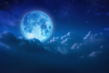 Full blue moon behind cloud over sky and star at night. Outdoors at night. Beautiful lunar shine moonlight over cloudy at nighttime with copy space background for headline text and graphic design. Zdjęcie Seryjne