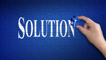 Solution word on Jigsaw puzzle ? business concept. Man hand holding a blue puzzle to complete the word Solution divided over them concept of the solution to a problem, challenge, plan and strategy.