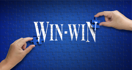 win win word on Jigsaw puzzle ? business concept. Man hand holding a blue puzzle to complete the word win-win divided over them concept of the solution to a problem, challenge, plan and strategy.