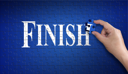 Finish word on Jigsaw puzzle – business concept. Man hand holding a blue puzzle to complete the word Finish divided over them concept of the solution to a problem, challenge, plan and strategy.