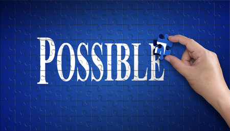 Possible word on Jigsaw puzzle – business concept. Man hand holding a blue puzzle to complete the word Possible divided over them concept of the solution to a problem, challenge, plan and strategy.