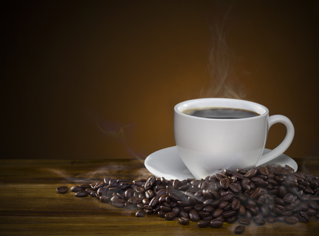 black hot coffee cup with roasted brown coffee beans and smoke on wooden table. coffee mug with raw coffee seeds with copy space good for text and graphic design.