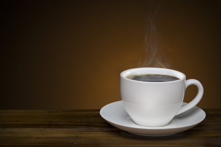 hot coffee cup on wooden table. black coffee with smoke with copy space good for text and graphic design Zdjęcie Seryjne