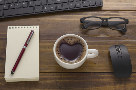 Love sign, Heart shape on Black coffee cup on office table. brown wooden work desk with business objects, notepad, notebook, computer Key broad, Mouse, Glasses - Top view
