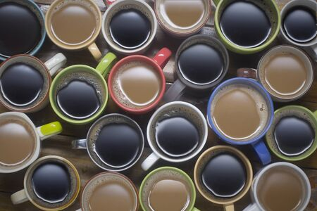 coffee time - lots of coffee in different cups. coffee lover - top view of many cups of coffee on wooden table good background for text or graphic design