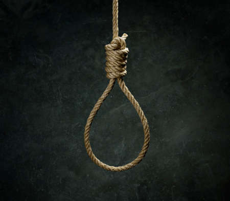 Rope noose for hangman made of natural fiber rope on a grainy gray wall. Hemp rope knot for gallows and Hang man over black concrete wall. The rope noose for homicide or commit suicide concept. Stock Photo