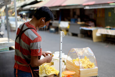 Bangkok, Thailand - January 4, 2015. Unidentified jack fruit seller is preparing the fruit for sell.