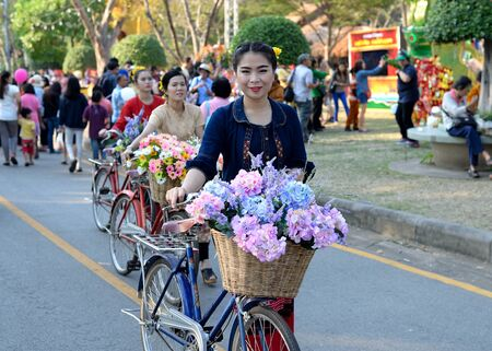 traditional custom: Bangkok, Thailand - January 17, 2015 Unidentified  Thai women in traditional custom with bicycle and flower at Lumpini Park, when the day of Thailands travel festival. Editorial