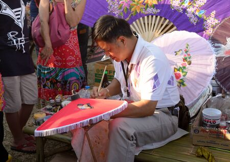 umbella: Bangkok, Thailand - January 17, 2015 Unidentified man is painting umbella at Lumpini Park, when the day of Thailands travel festival.