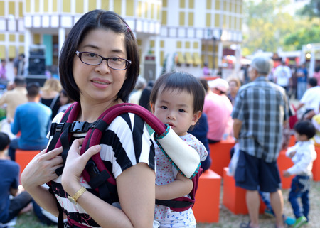 lumpini: Bangkok, Thailand - January 17, 2015 Unidentified mother and her daughter at Lumpini Park, when the day of Thailands travel festival.